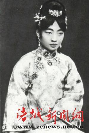 """婉容身穿黄缎织锦满族旗袍,梳起高高的满族式""""两把头"""",外国使节夫人无"""